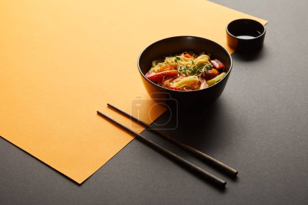 Photo for Noodles with shrimps and vegetables in bowl near chopsticks, soy sauce on black and yellow background - Royalty Free Image