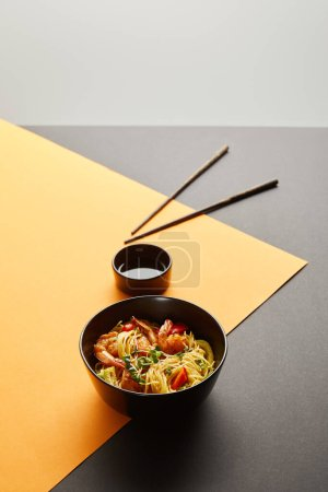selective focus of noodles with shrimps and vegetables in bowl near chopsticks, soy sauce on black and yellow background isolated on grey