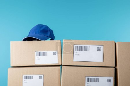Photo for Cap on cardboard boxes with qr and barecodes isolated on blue - Royalty Free Image