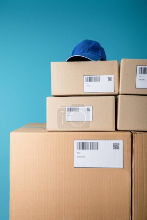 Photo for Cap on stacked cardboard boxes with qr and barecodes isolated on blue - Royalty Free Image