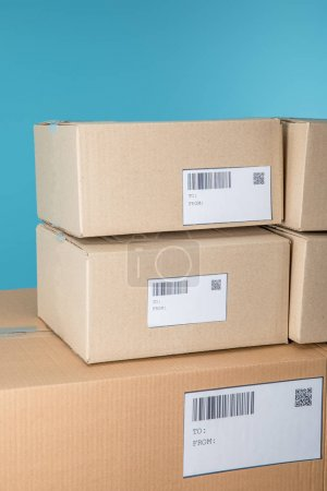 Photo for Stacked cardboard packages with barcodes and qr codes isolated on blue - Royalty Free Image