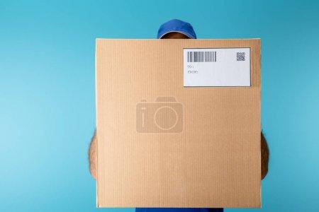 Photo pour Messager tenant une boîte en carton avec qr et code à barres isolée sur bleu - image libre de droit