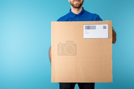 Photo for Cropped view of courier holding cardboard box with qr and barcode on card isolated on blue - Royalty Free Image