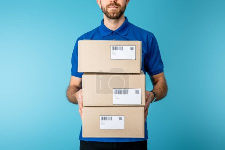 Photo for Cropped view of courier holding cardboard packages with qr codes and barcodes on cards isolated on blue - Royalty Free Image