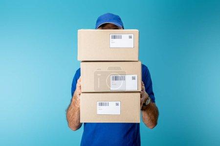 Photo pour Agent de livraison tenant des colis en carton avec codes à barres et codes qr isolés en bleu - image libre de droit