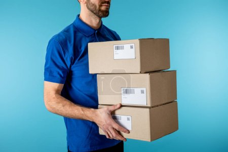 Photo for Cropped view of delivery man holding cardboard packages isolated on blue - Royalty Free Image