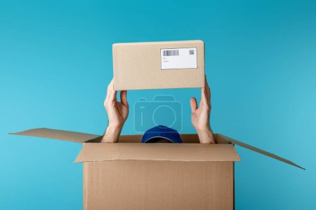Photo for Cropped view of courier in cap holding cardboard package from box isolated on blue - Royalty Free Image