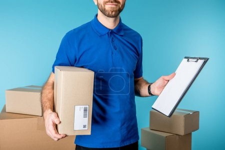 Photo for Cropped view of delivery man holding cardboard box and clipboard with copy space near boxes isolated on blue - Royalty Free Image