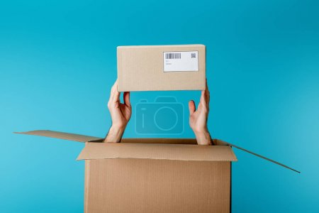 Photo for Cropped view of courier holding cardboard box from package isolated on blue - Royalty Free Image
