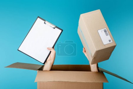 Hands of courier holding clipboard and package from cardboard box isolated on blue