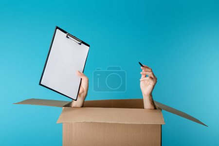 Photo for Hands of courier holding clipboard and pen from cardboard box isolated on blue - Royalty Free Image