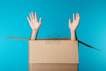 Photo for Hands of courier in cardboard package isolated on blue - Royalty Free Image