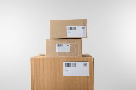 Photo for Stacked cardboard boxes with barcodes and qr codes on cards isolated on grey - Royalty Free Image