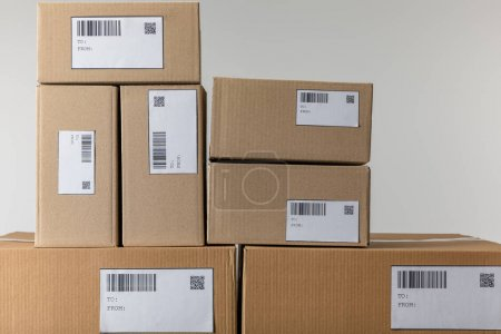 Photo for Stacked cardboard boxes with barcodes and qr codes isolated on grey - Royalty Free Image
