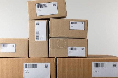 Photo pour Cartes avec qr et codes à barres sur boîtes en carton empilées isolées sur gris - image libre de droit