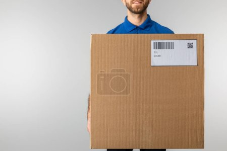 Photo for Cropped view of bearded courier holding cardboard package with qr code and barcode isolated on grey - Royalty Free Image