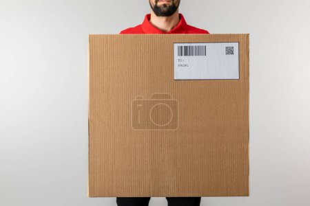 Photo for Cropped view of courier holding package with barcode and qr code on card isolated on grey - Royalty Free Image