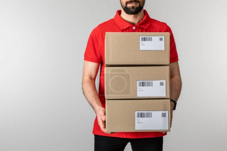 Photo for Cropped view of bearded courier holding boxes with barcodes and qr codes on cards isolated on grey - Royalty Free Image