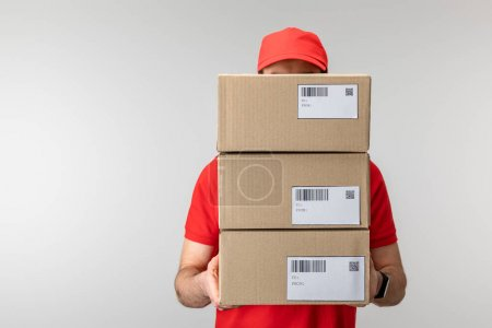 Photo for Delivery man in uniform holding cardboard boxes isolated on grey - Royalty Free Image