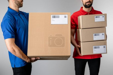 Photo for Cropped view of couriers holding cardboard boxes isolated on grey - Royalty Free Image