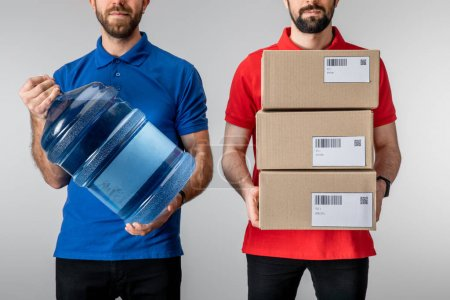 Photo for Cropped view of couriers holding cardboard packages and bottled water isolated on grey - Royalty Free Image