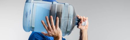 Photo for Side view of courier carrying on shoulder bottled water isolated on grey, panoramic shot - Royalty Free Image