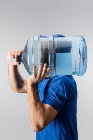 Photo for Side view of courier carrying on shoulder bottled water isolated on grey - Royalty Free Image