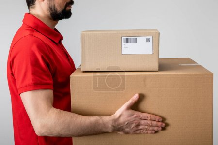 Photo for Side view of courier carrying cardboard boxes isolated on grey - Royalty Free Image