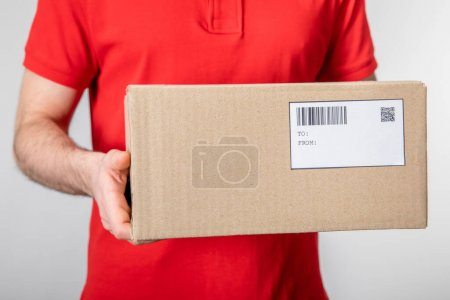 Photo for Cropped view of courier carrying cardboard box with barcode and qr code on card isolated on grey - Royalty Free Image
