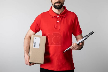 Photo for Cropped view of bearded courier holding clipboard and cardboard package isolated on grey - Royalty Free Image