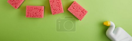 Photo for Panoramic shot of pink sponges and bottle with toilet cleaner on green - Royalty Free Image