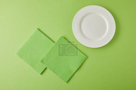 Photo pour Vue du dessus de la plaque blanche et des chiffons pour laver la vaisselle en vert - image libre de droit