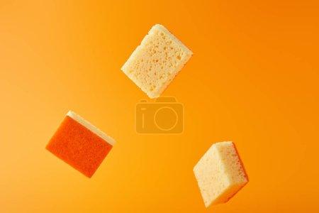 Photo pour Éponges jaunes tombantes pour le lavage des plats isolées sur orange - image libre de droit