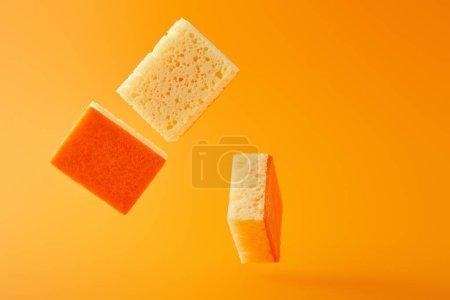 Photo pour Éponges tombantes pour le nettoyage des maisons isolées sur orange - image libre de droit