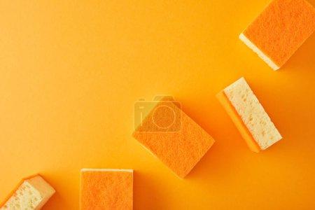 Photo pour Vue de dessus des éponges pour le lavage des plats sur orange - image libre de droit
