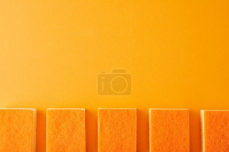 Photo for Flat lay with row of sponges for house cleaning on orange - Royalty Free Image