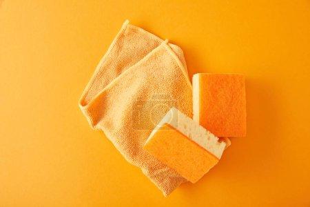 Photo pour Vue de dessus de chiffon et éponges jaunes pour le nettoyage de la maison sur orange - image libre de droit