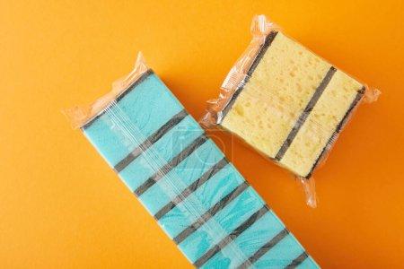 Photo pour Vue du haut des éponges bleues et jaunes emballées pour le nettoyage de la maison sur orange - image libre de droit