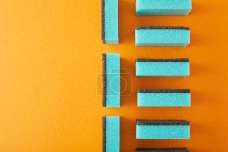 Photo pour Vue de dessus des éponges bleues pour le lavage des plats sur orange - image libre de droit