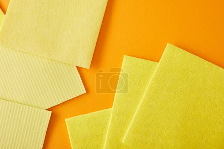 Photo pour Vue de dessus des chiffons jaunes pour le nettoyage de la maison sur orange - image libre de droit