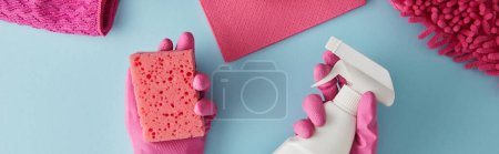 Photo for Panoramic shot of housekeeper in pink rubber gloves holding sponge and spray bottle on blue with rags - Royalty Free Image