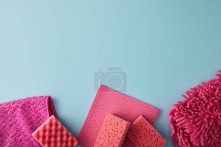 Photo pour Vue de dessus des éponges roses et des chiffons pour le nettoyage de la maison sur bleu - image libre de droit