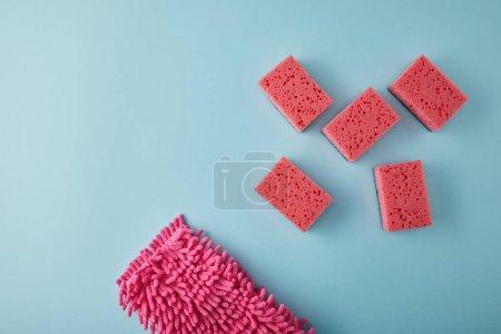Photo pour Vue du dessus des articles ménagers roses pour le nettoyage de la maison sur bleu - image libre de droit
