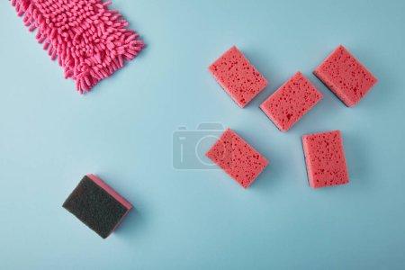 Photo pour Vue de dessus des fournitures de nettoyage rose sur bleu - image libre de droit