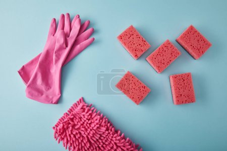 Photo for Top view of pink rubber gloves, rag and sponges for house cleaning on blue - Royalty Free Image