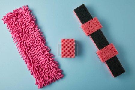 Photo pour Vue de dessus du chiffon rose et des éponges pour le nettoyage de la maison sur bleu - image libre de droit