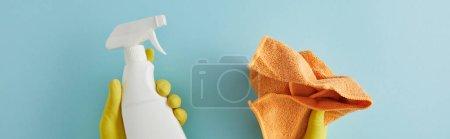 Photo pour Prise de vue panoramique de la femme de ménage dans des gants en caoutchouc tenant bouteille de pulvérisation et chiffon sur bleu - image libre de droit