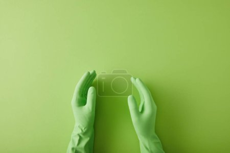 Photo for Cropped view of hands of housekeeper in rubber gloves on green - Royalty Free Image