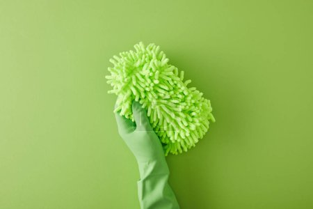 top view of housekeeper in rubber glove holding rag on green