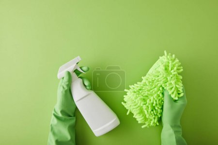 Photo for Top view of housekeeper in rubber gloves holding spray bottle and rag on green - Royalty Free Image